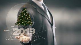 2019 nuove tecnologie disponibile di Holding dell'uomo d'affari dell'albero di Natale Immagine Stock Libera da Diritti