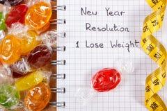 Nuovi anni di risoluzioni scritte in taccuino, in caramelle e nella misura di nastro Fotografie Stock Libere da Diritti
