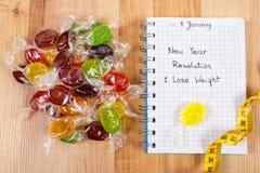 Nuovi anni di risoluzioni scritte in taccuino, in caramelle e nella misura di nastro Immagini Stock Libere da Diritti