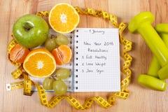 Nuovi anni di risoluzioni scritte in taccuino ed in frutti, teste di legno con il centimetro Fotografie Stock Libere da Diritti