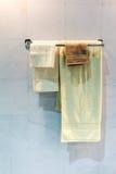 Nuovi asciugamani piegati gialli e marroni che appendono sulla ferrovia del metallo al di sotto della l fotografia stock libera da diritti