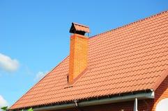 Nuovi mattonelle di tetto del metallo e fumaiolo rossi contro cielo blu Fotografia Stock Libera da Diritti