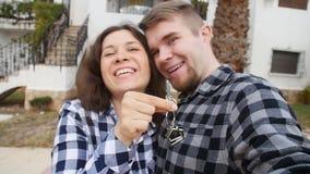 Nuovi proprietari di abitazione con selfie chiave Bene immobile, nuova casa o appartamento e concetto della gente video d archivio
