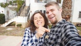 Nuovi proprietari di abitazione con selfie chiave Bene immobile, nuova casa o appartamento e concetto della gente archivi video