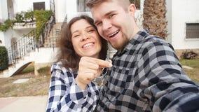 Nuovi proprietari di abitazione con selfie chiave Bene immobile, nuova casa o appartamento e concetto della gente stock footage