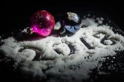 Nuovo 2018 anni con i numeri, abete, palle del fondo in neve Fondo di buio del fuoco selettivo Fotografia Stock