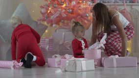 Nuovo anno di mattina I bambini stanno sedendo dal Natale meravigliosamente decorato stock footage