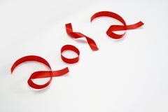Nuovo anno felice in nastri rossi Immagine Stock