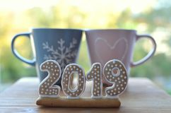 Nuovo anno 2019 Il pan di zenzero dipende un bordo di legno Saluti di nuovo anno Adatto come fondo Due tazze Insieme nel nuovo immagine stock libera da diritti