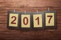 Nuovo anno 2017 nel telaio della foto che appende sulla corda da bucato Fotografia Stock Libera da Diritti