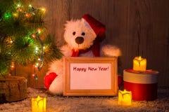 Nuovo anno, orso di Natale che si siede sotto un albero di abete con una struttura di legno con il nuovo anno dell'iscrizione! fotografia stock libera da diritti