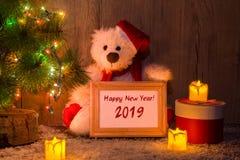 Nuovo anno, orso di Natale che si siede sotto un albero di abete con una struttura di legno con il nuovo anno dell'iscrizione! immagini stock libere da diritti
