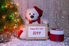 Nuovo anno, orso di Natale che si siede sotto un albero di abete con una struttura di legno con il nuovo anno dell'iscrizione! immagine stock