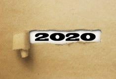 Nuovo anno rivelante 2020 della carta strappata o lacerata su bianco immagine stock libera da diritti