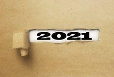 Nuovo anno rivelante 2021 della carta strappata o lacerata su bianco immagini stock