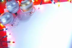Nuovo bordo delle bagattelle di natale con gli indicatori luminosi di festa. Fotografia Stock