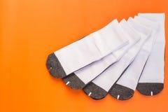 Nuovo calzino bianco dello studente su fondo arancio con spazio libero per Fotografia Stock