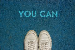 Nuovo concetto di vita, scarpe di sport e la parola POTETE scritto sulla terra del passaggio pedonale, slogan motivazionale royalty illustrazione gratis