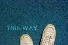 Nuovo concetto di vita, slogan motivazionale con la parola QUESTO MODO sul terreno del modo della passeggiata fotografia stock