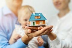 Nuovo concetto domestico - giovane famiglia con il modello di scala della casa di sogno Fotografia Stock