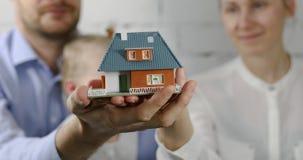 Nuovo concetto domestico - giovane famiglia con il modello di scala della casa di sogno in mani video d archivio