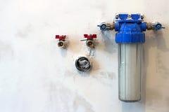 Nuovo del filtro da acqua installato su una parete della cucina per purificare bere Immagini Stock