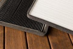 Nuovo e vecchio filtro dell'aria dell'automobile sulla tavola di legno Fine in su fotografia stock