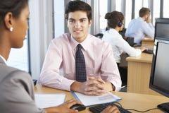 Nuovo impiegato che inizia lavoro in ufficio occupato Immagine Stock