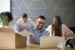 Nuovo impiegato maschio millenario sorridente che disimballa scatola al wor dell'ufficio fotografie stock