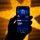Nuovo iPhone di Apple contro la stella defocused blu che caratterizza bellezza a Immagine Stock Libera da Diritti