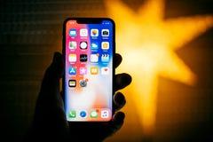 Nuovo iPhone di Apple contro la stella defocused blu che caratterizza i apps domestici Immagini Stock