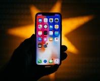 Nuovo iPhone di Apple contro la stella defocused blu che caratterizza scre domestico Fotografie Stock Libere da Diritti