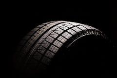 Nuovo pneumatico dell'automobile su una priorità bassa nera Fotografia Stock Libera da Diritti