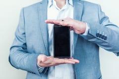 Nuovo telefono brillante in mani maschii Fotografia Stock