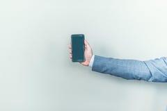 Nuovo telefono brillante in mani maschii Fotografie Stock Libere da Diritti