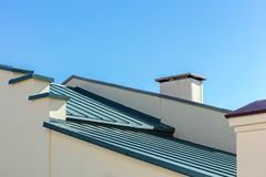 Nuovo tetto ondulato grigio del metallo contro il fondo del cielo blu fotografie stock libere da diritti