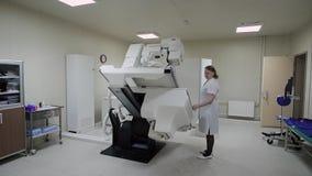 Nuovo ufficio medico moderno con varia attrezzatura elettronica dentro Un medico femminile regola la macchina di raggi x a lavoro archivi video