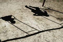 Nur der Schatten von zwei Kindern ist sichtbare Kinder fahren auf ein Schwingen Stockfoto