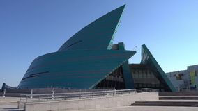 Nur-Sultan concert hall. Nur-Sultan Astana Kazakhstan central concert hall frontal view on a sunny cloudy blue sky day stock footage