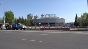 Nur-sultan concert hall. Road workers work at the road in front of Nur-Sultan Astana Concert Hall while cars are passing through on a sunny blue sky day stock video