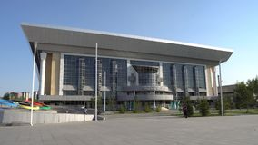 Nur-Sultan sports complex. Nur-Sultan Astana Daulet sports complex frontal view with walking people and children driving bicycles on a sunny blue sky day stock footage