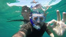 Nurek nurkuje pod wodą i robi OK znakowi zbiory