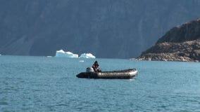 Nurek unosi się w gumowej łodzi na tle góry lodowa, lód, w Arktycznym oceanie zbiory wideo