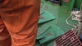 Nurek w pomarańczowym nurkowym kostiumu usuwa flippers po nurkować w morze zbiory