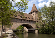 Nuremberg. Historical building with tower in Nuremberg. Brick arch over river, with trees around Royalty Free Stock Photo