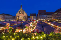 Nuremberg-Germany-Christmas Market-evening cityscape. Nuremberg, Germany- beautiful evening scenery with church, blue sky, crowd people, stalls side by side royalty free stock photos