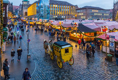 Nuremberg, Germany-Christmas time- Main Market Square. Christmas Market (Christkindlesmarkt) - yellow stagecoach tour, lot of people, stalls-Nuremberg (Nuernberg royalty free stock photo