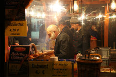 NUREMBERG, GERMANY - DECEMBER 22, 2013: Stylish salesman sells sausages at night at the Christmas fair, Nuremberg, Germany stock image