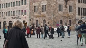 NUREMBERG, GERMANY - November 30, 2019: Left to right pan real time wide shot of people walking on the square in. Nuremberg, November 30, 2019 in Nuremberg stock footage