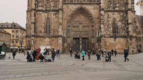 NUREMBERG, GERMANY - November 30, 2019: Real time wide shot of people walking in the square and listening to street stock footage